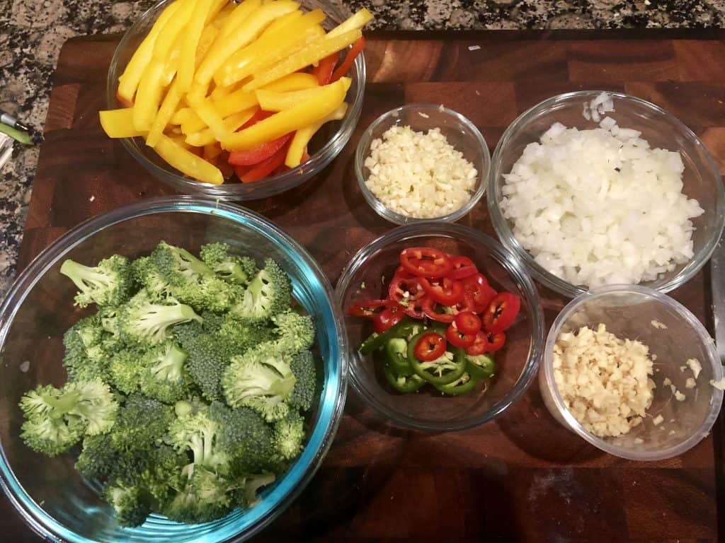 diced onion, minced garlic and ginger, broccoli, and red bell peppers in seperate bowls on a cutting board