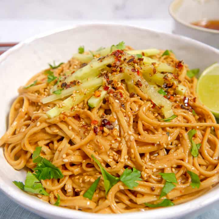 white bowl of cold sesame noodles topped with chili oil, green onions, and cucumber slices on a blue towel