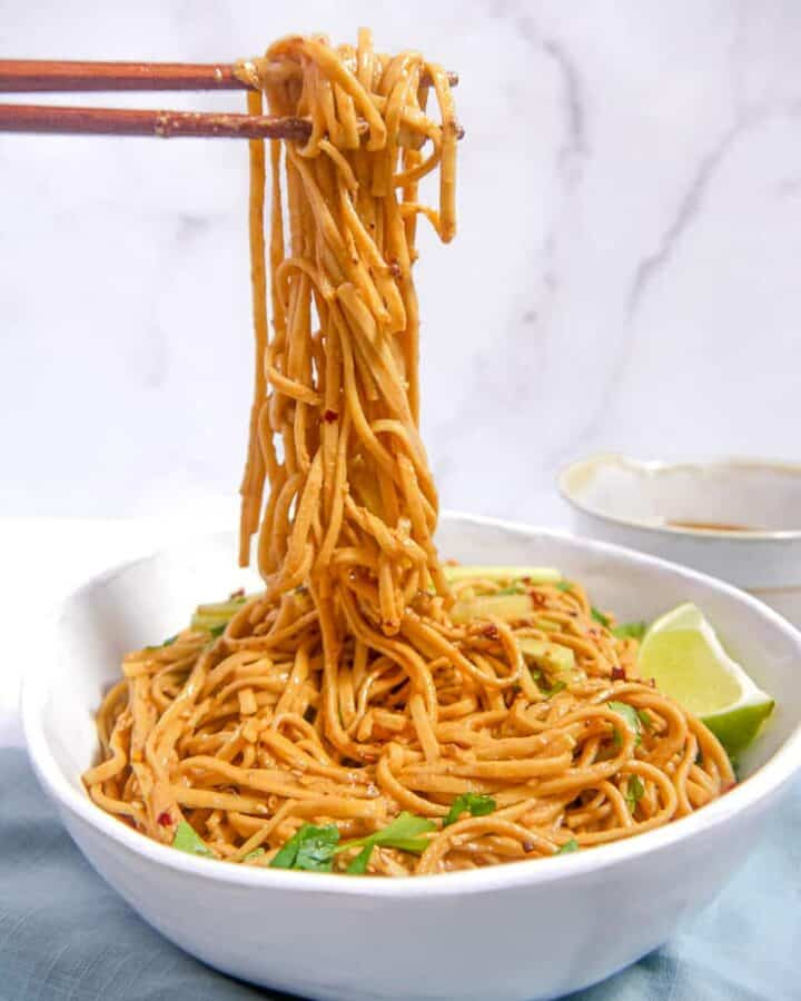 a white bowl full of sesame noodles, chopsticks lifting noodles out of the bowl into the air