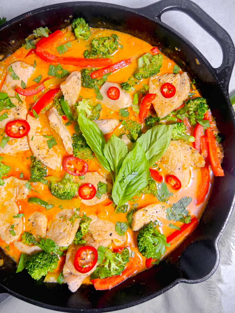 close up of cast iron skillet with red curry, chicken, basil leaves and sliced peppers on top