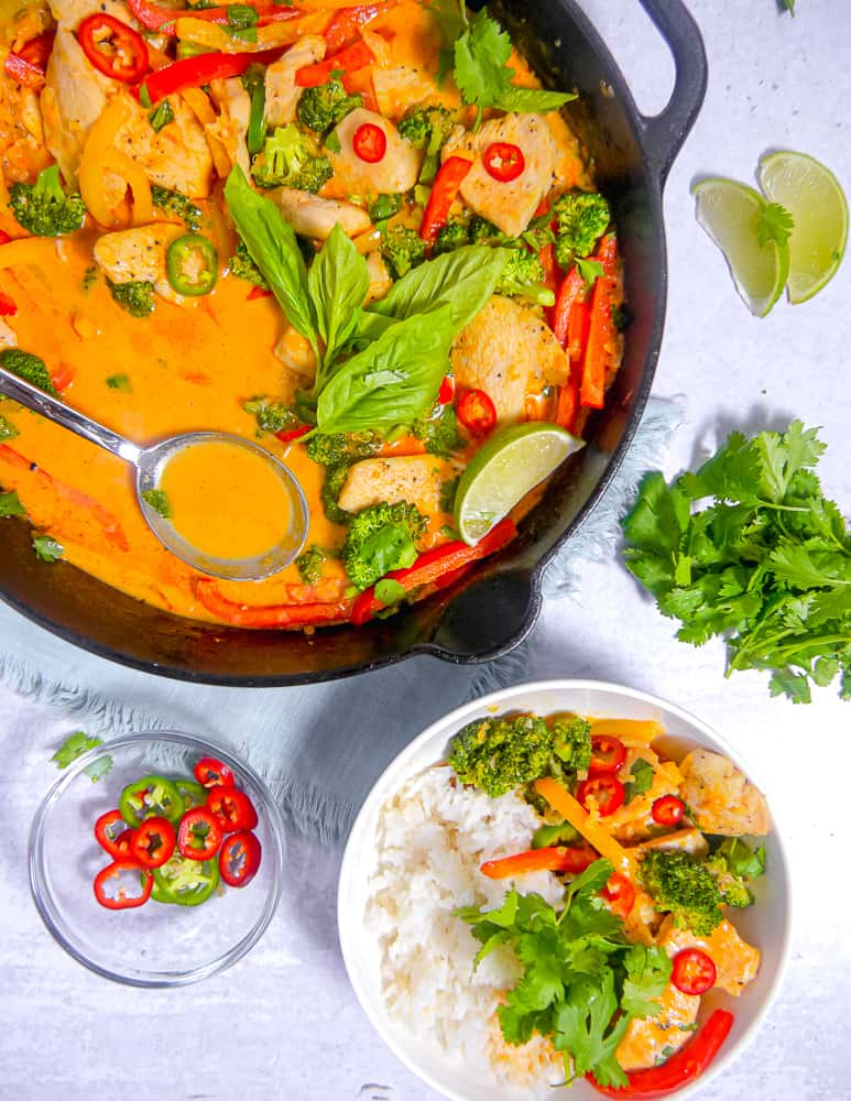 overhead photo of a cast iron skillet with red curry, chicken, asil, and sliced peppers, with a bowl of rice and red curry next to it