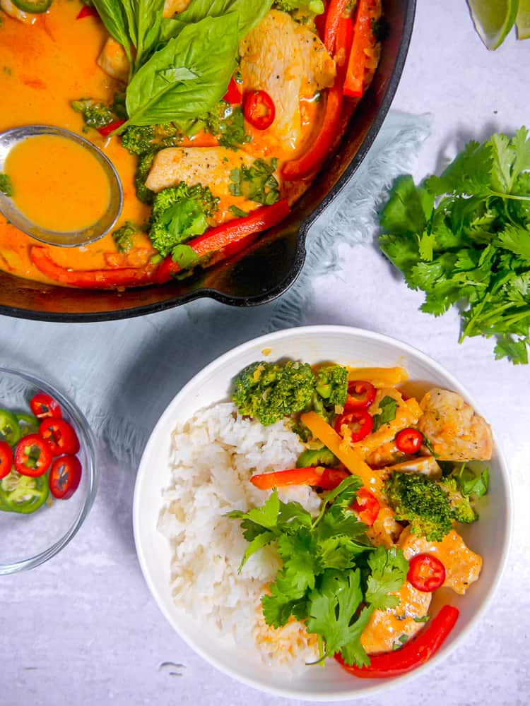 zoomed in bowl of rice with red curry chicken on the side and fresh herbs surrounding