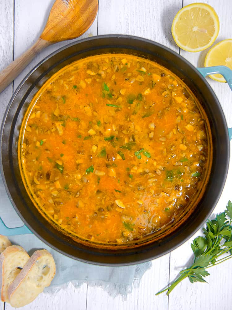 overhead photo of soup pot with vegetable orzo soup surrounded by bread, lemons, parsley and spoon