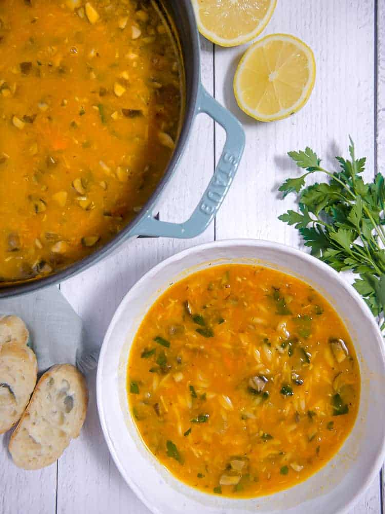 pot with vegetable orzo soup next to bowl filled with soup and bread, herbs, and lemons in background