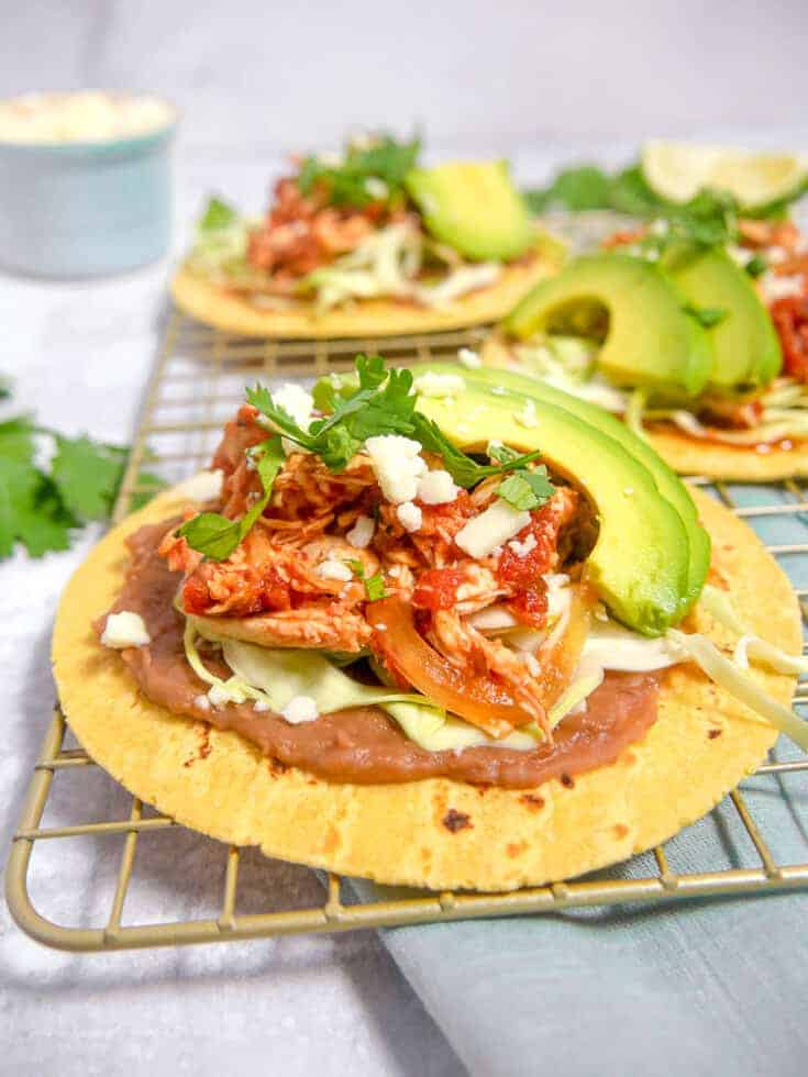 close up of shredded chicken tinga on corn tortillas with refried beans, lettuce, and avocado