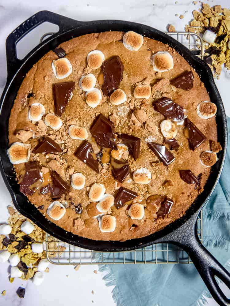 overhead photo of large s'mores cookie in a cast iron skillet with melted chocolate, toasted marshmallows, and graham crackers on top