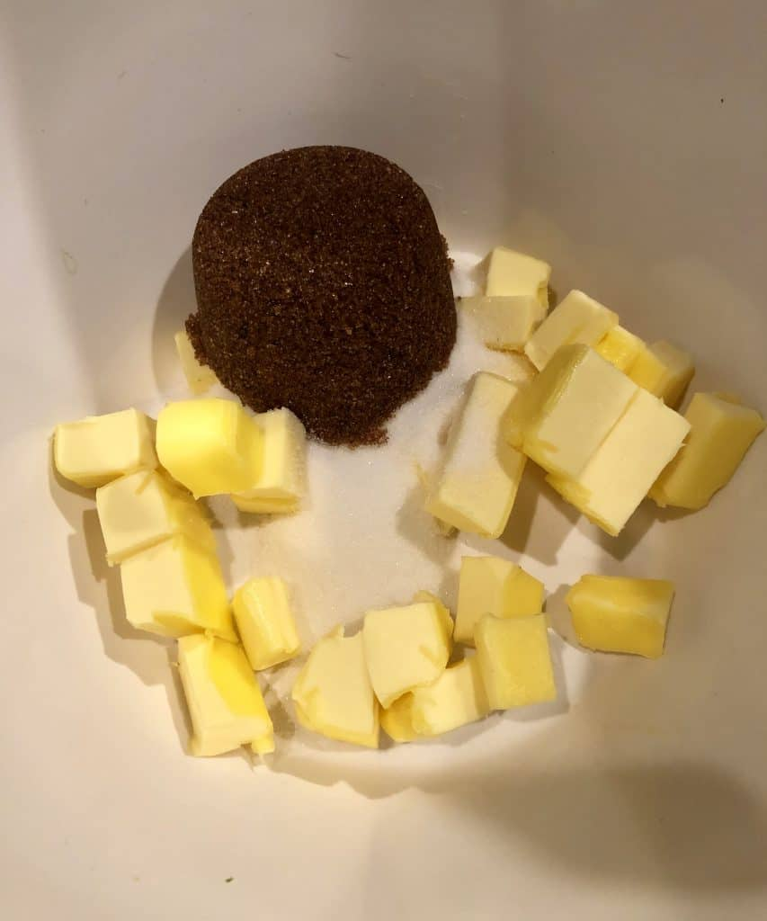 cubed butter, brown sugar, and white sugar in a white bowl
