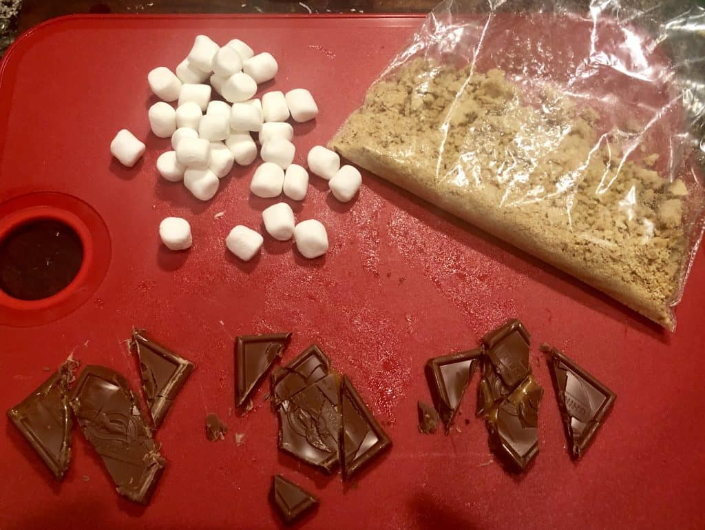 cutting board with marshmallows, chocolate and crushed graham