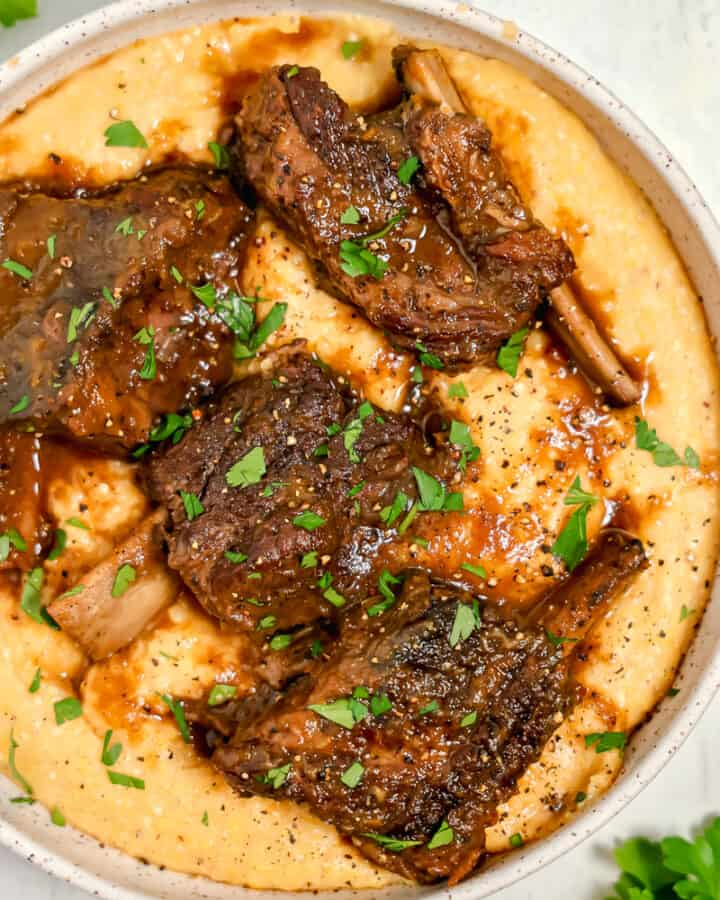 bowl of polenta with 4 beef short ribs and gravy on top