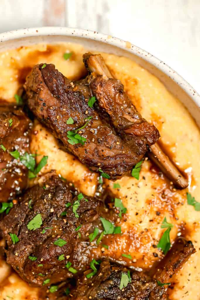 bowl of polenta with short ribs on top and gravy