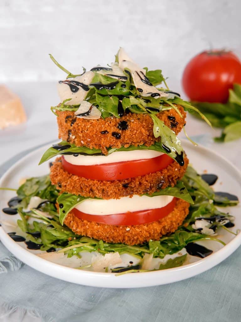 a stack of crispy eggplant, tomato, mozzarella, arugula salad, piled high on a white plate with a red tomato, basil, and parmesan cheese block in the background