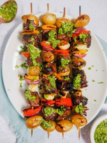 Steak kabobs with potatoes, peppers, onions, and garlic cloves, on a skewer with chimichurri sauce drizzled oer the top on a white plate