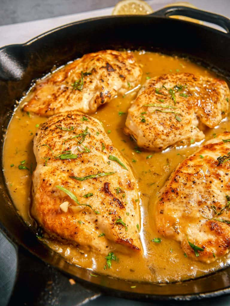 close up on a chicken breast in a tarragon mustard sauce in a cast iron skillet