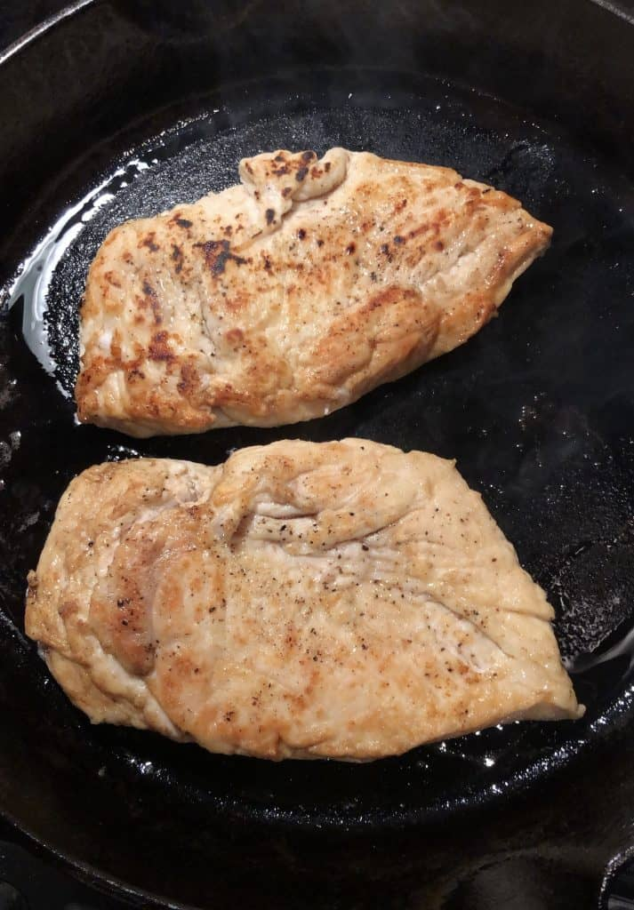 seared chicken breasts in a cast iron skillet