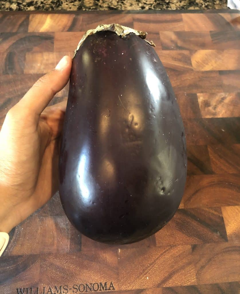 holding a whole eggplant in hand over a wooden cutting board