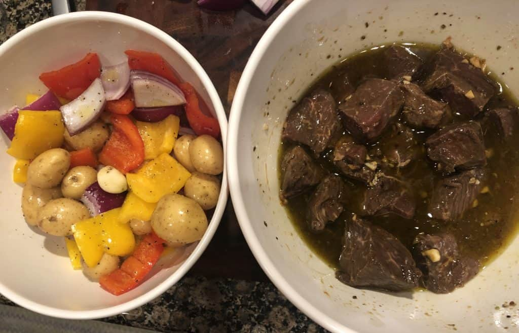 two white bowls, one with seasoned vegetables and one with marinating sirloin steak