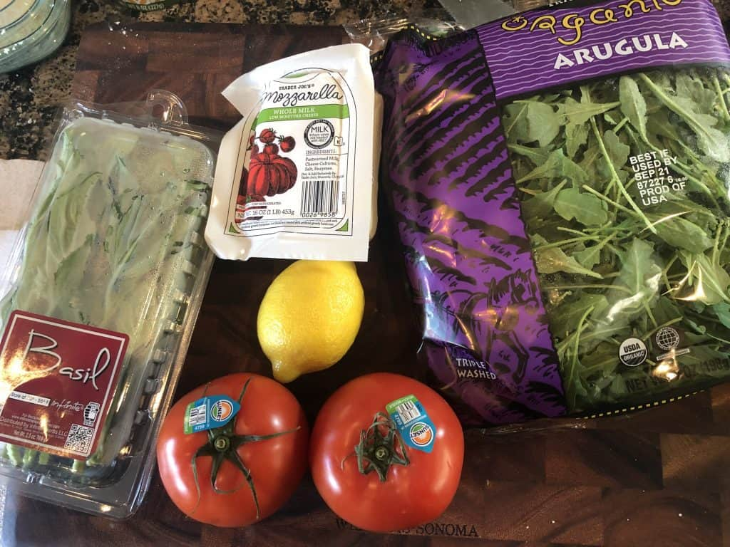 bag of arugula, two tomatoes, lemon, mozzarella log, and basil pack on a cutting board