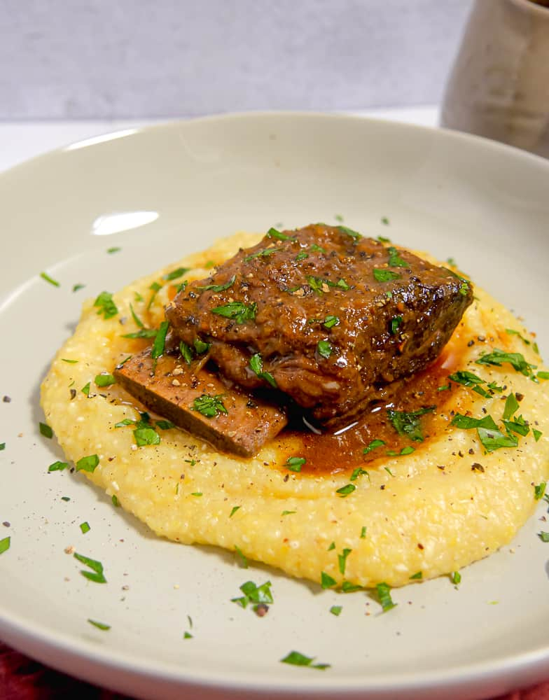 plate with yellow polenta and a short rib on top surrounded by gravy and fresh parsley
