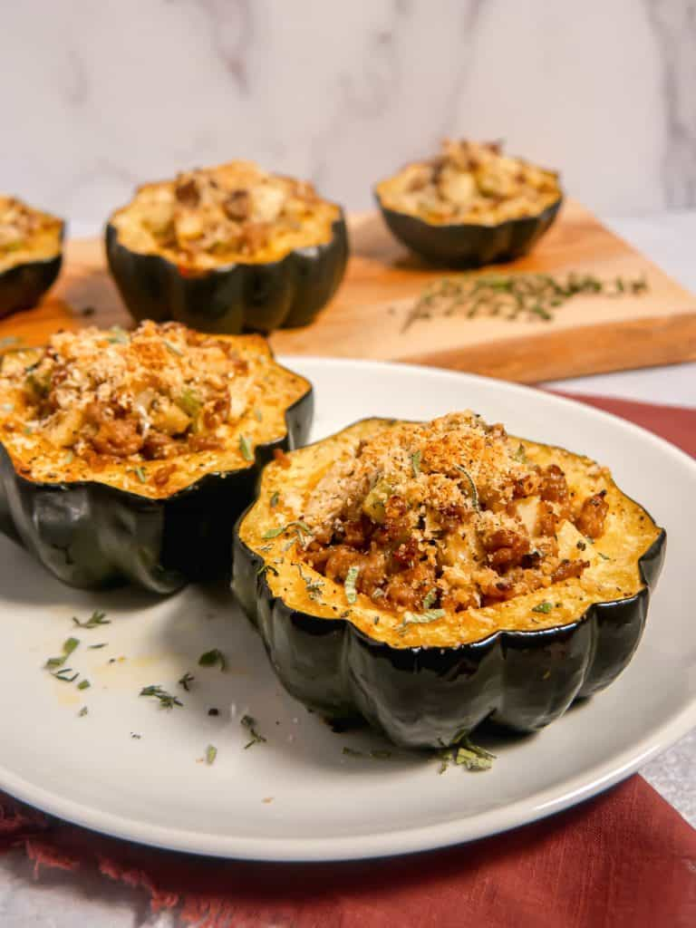 two stuffed acorn squashes on a white plate with additional stuffed squash in the background