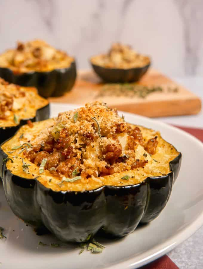 Close up of a stuffed acorn squash on a white plate with more stuffed squash blurred in the background