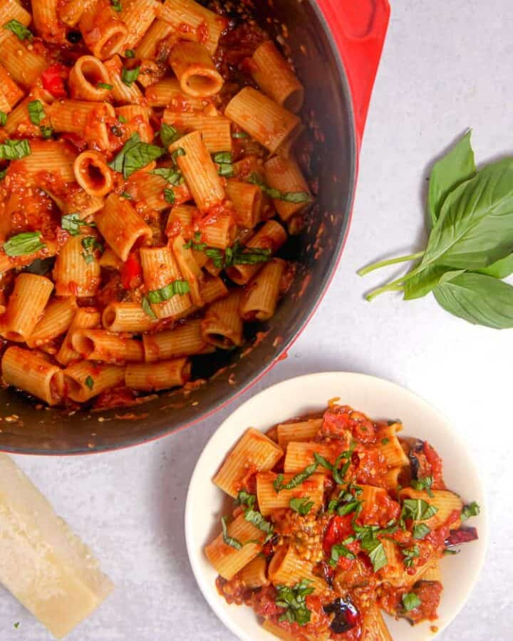 Red dutch oven filled with rigatoni, bell pepper, and eggplant, a white bowl filled with pasta and basil leaves on top