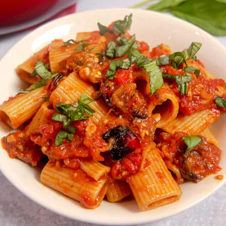 white bowl with rigatoni, red sauce, roasted eggplant an roasted bell peppers topped with basil chopped