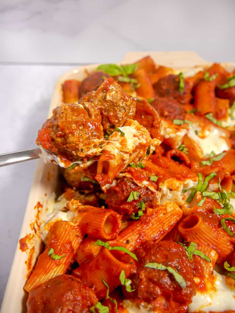meatballs being lifted out of a baking dish with silver spoon