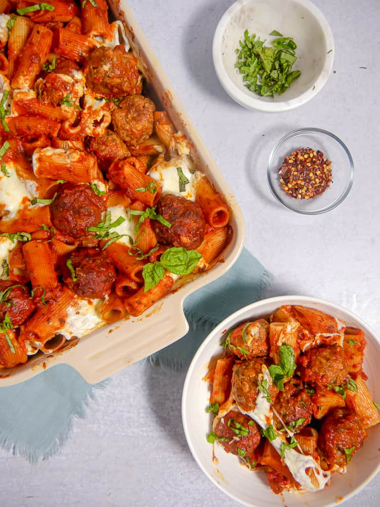 baking dish next to whit bowl filled with rigatoni,meatballs, red sauce, and melted cheese
