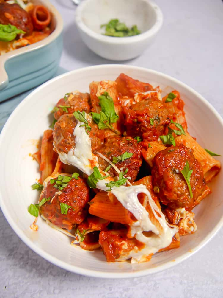 white bowl of meatballs and pasta with cheese stretched across