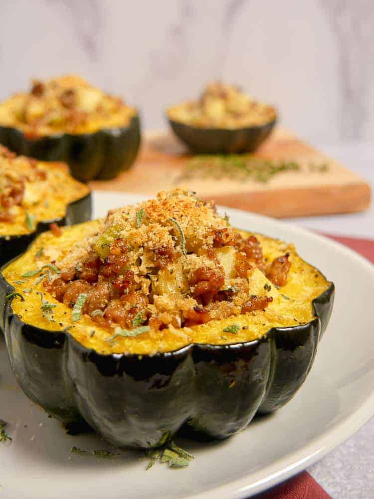 stuffed acorn squash with apples and sausage on a white plate