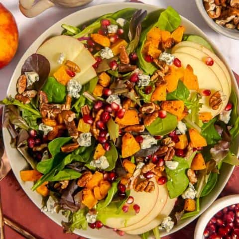 Overhead photo of harvest salad with roasted butternut squash, apples, blue cheese, pecans, pomegranate seeds, on a red towel with small bowls around