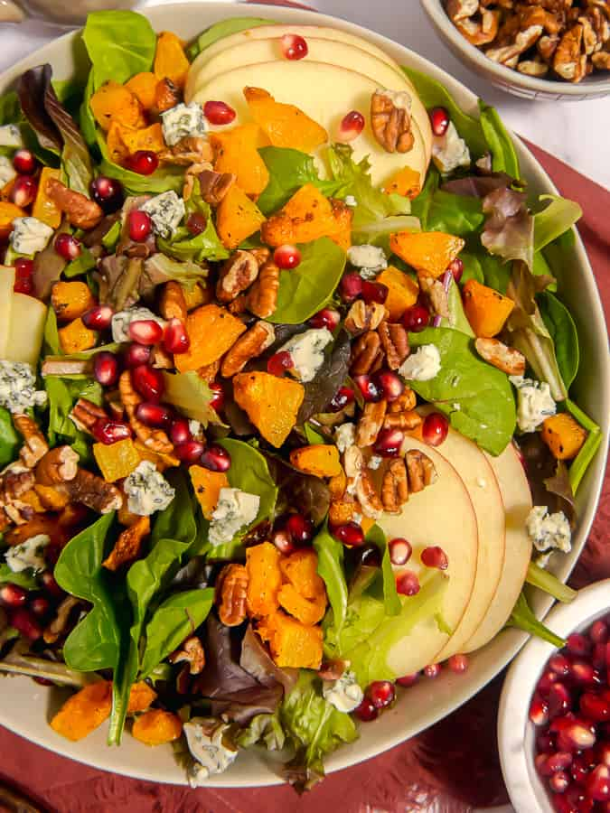 close up photo of salad with apples, blue cheese, butternut squash and pomegranate seeds