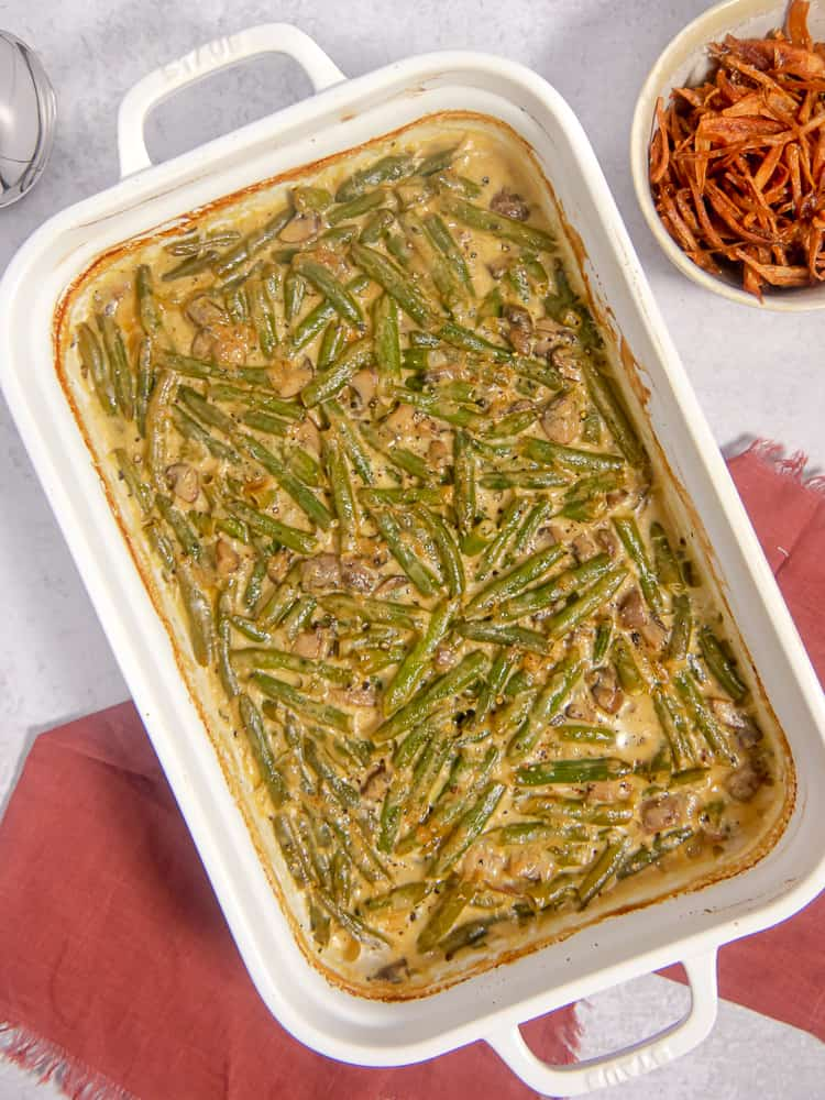 overhead photo of green bean casserole in a white baking dish on a red napkin