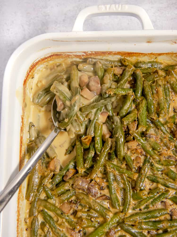 close up of green bean casserole being spooned out of white baking dish