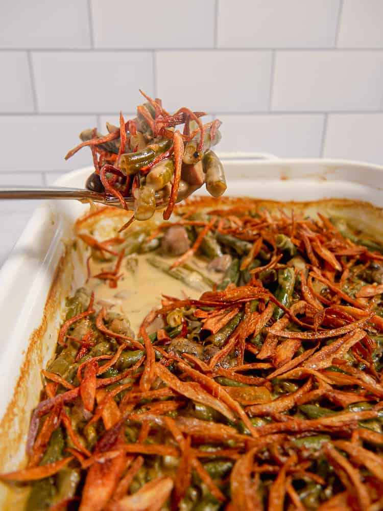 green bean casserole topped with fried shallots being spooned out of white baking dish