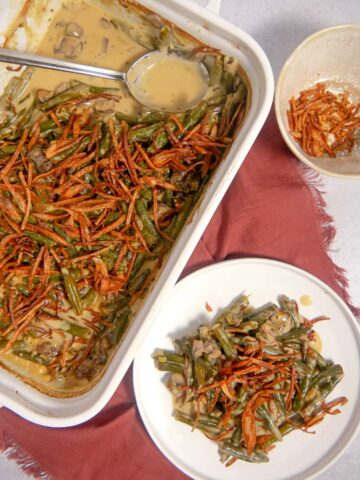 overhead photo of a baking dish with green bean casserole, a plate of green bean casserole, and a bowl of fried shallot