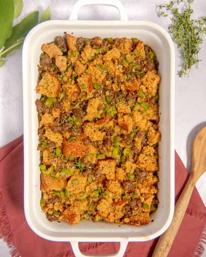 white baking dish with cornbread, sausage, apples, celery stuffing with red napkin, fresh herbs in background
