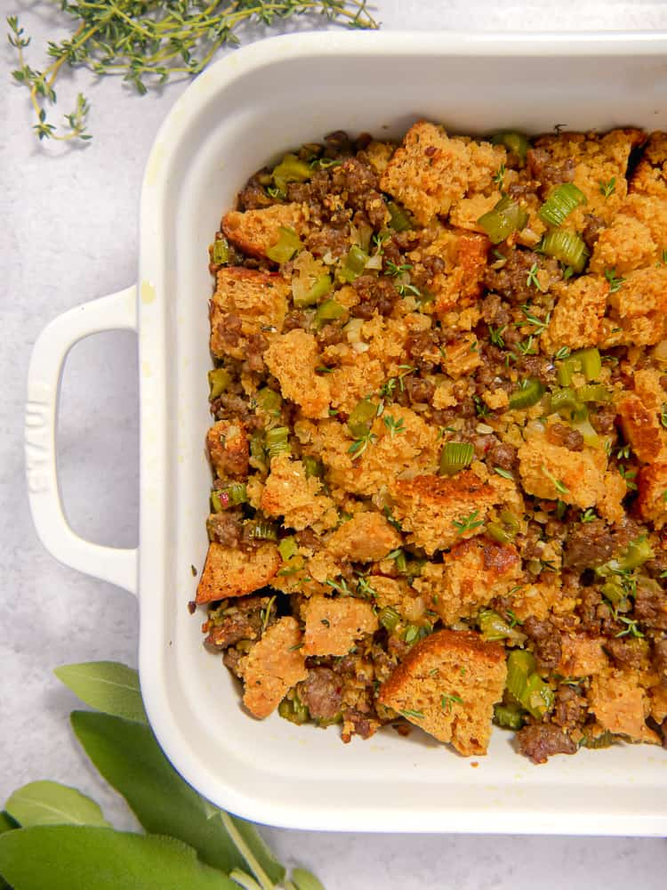close up of cornbread and sausage stuffing in a white baking dish with celery