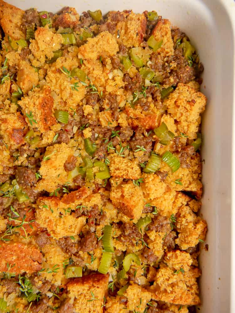 close up of cornbread, sausage, celery,apple stuffing in a white baking dish
