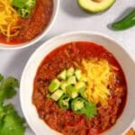two white bowls filled with chili topped with shredded cheese, avocado, and cilantro