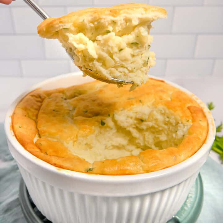soufflé dish with mashed potato soufflé being lifted out with a spoon