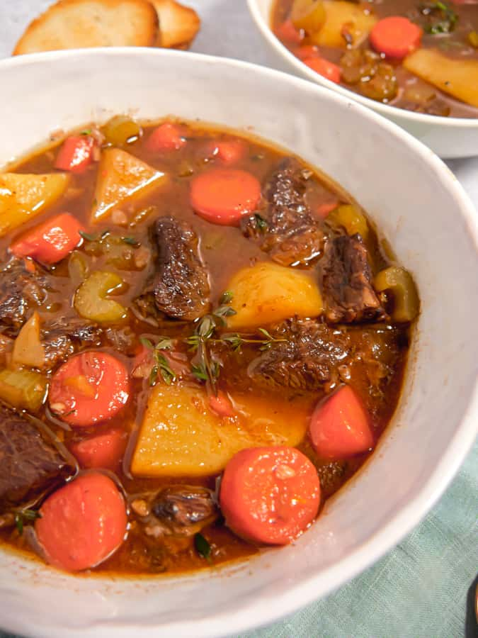 photo of two bowls of slow cooked guinness beef stew with bread slices