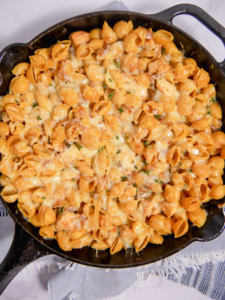 cast iron skillet with pasta shells covered in melted cheese and caramelized onions