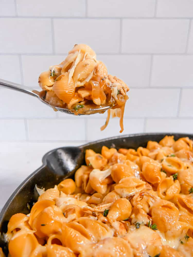 a spoon lifting pasta with cheese and caramelized onions out of a cast iron skillet