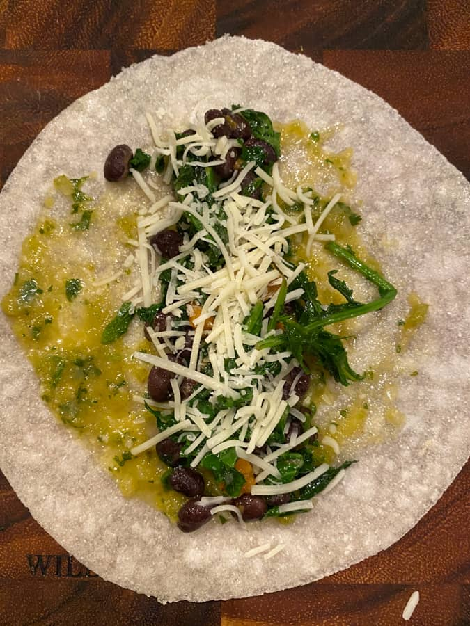tortilla with salsa verde, beans, sweet potato, kale, and cheese on top