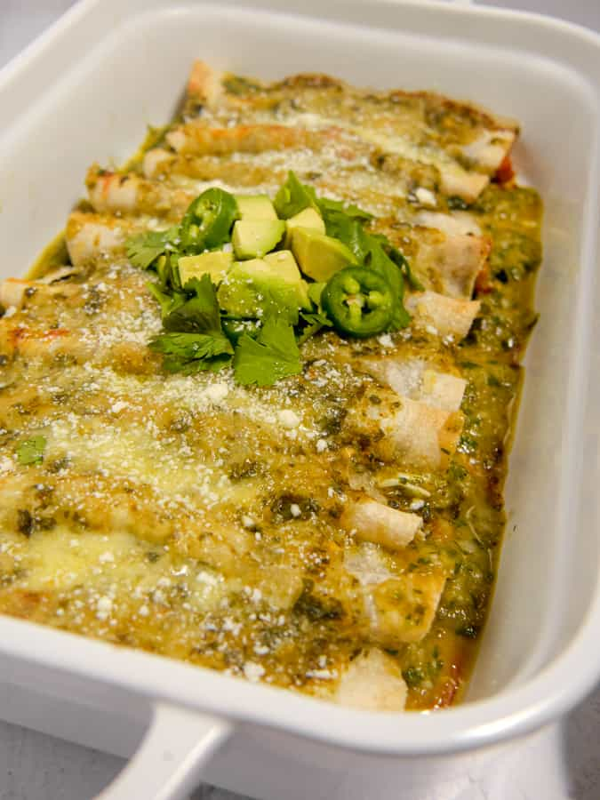 side shot of verde enchiladas in a white baking dish