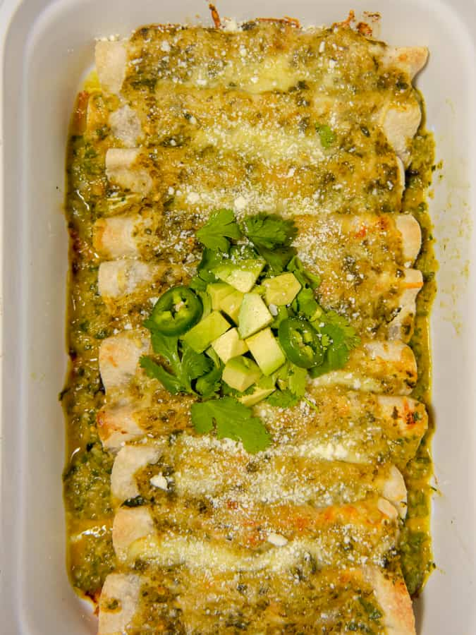close up of enchiladas topped with cilantro and avocado