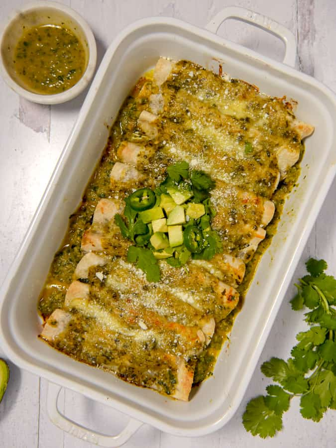 overhead shot of enchiladas in a white baking dish with verde sauce, cilantro, and avocado over melty cheese