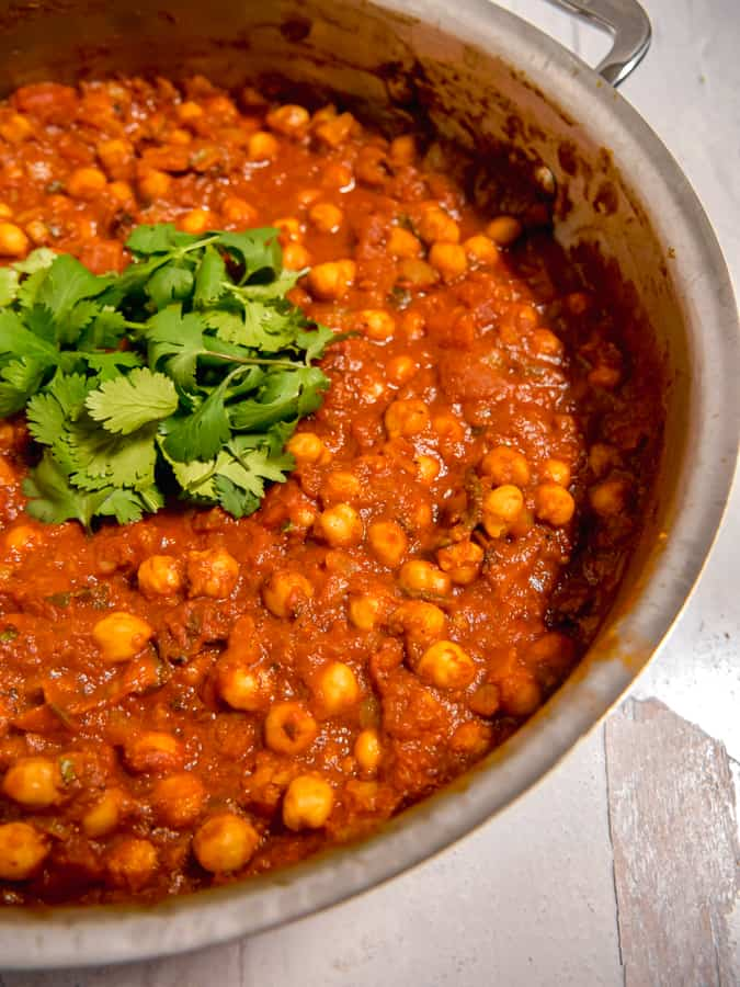 close up of chickpeas in spicy tomato sauce in a skillet