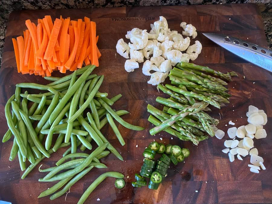 overhead photo of sliced carrots, green beans, cauliflower, asparagus, and garlic on a cutting board